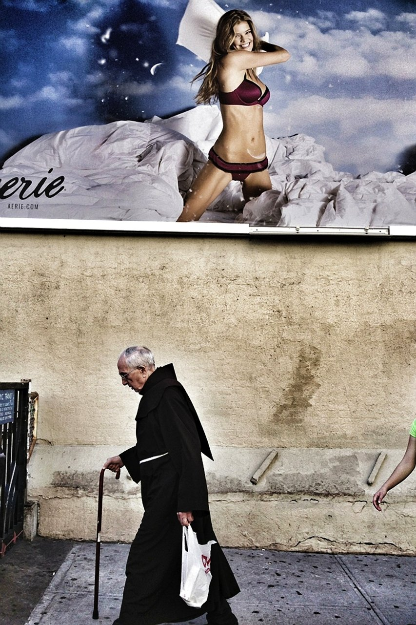 a-priest-walks-by-a-risqu-advertisement-in-this-photo-by-emanual-faria-of-portugal