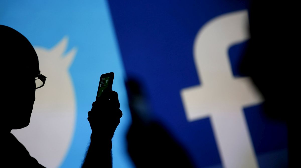 Men are silhouetted against a video screen with Facebook and Twitter logos as they pose with a Nokia Lumia 820 and Samsung Galaxy S4 in this photo illustration taken in the central Bosnian town of Zenica, August 14, 2013. REUTERS/Dado Ruvic (BOSNIA AND HERZEGOVINA - Tags: BUSINESS TELECOMS)