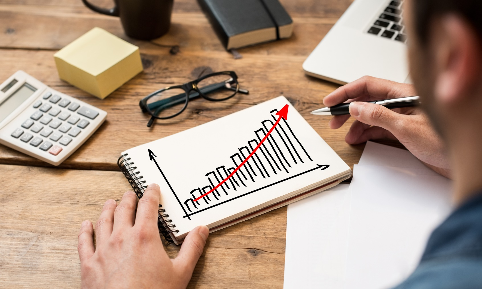 Businessman drawing a growing chart on a paper notebook