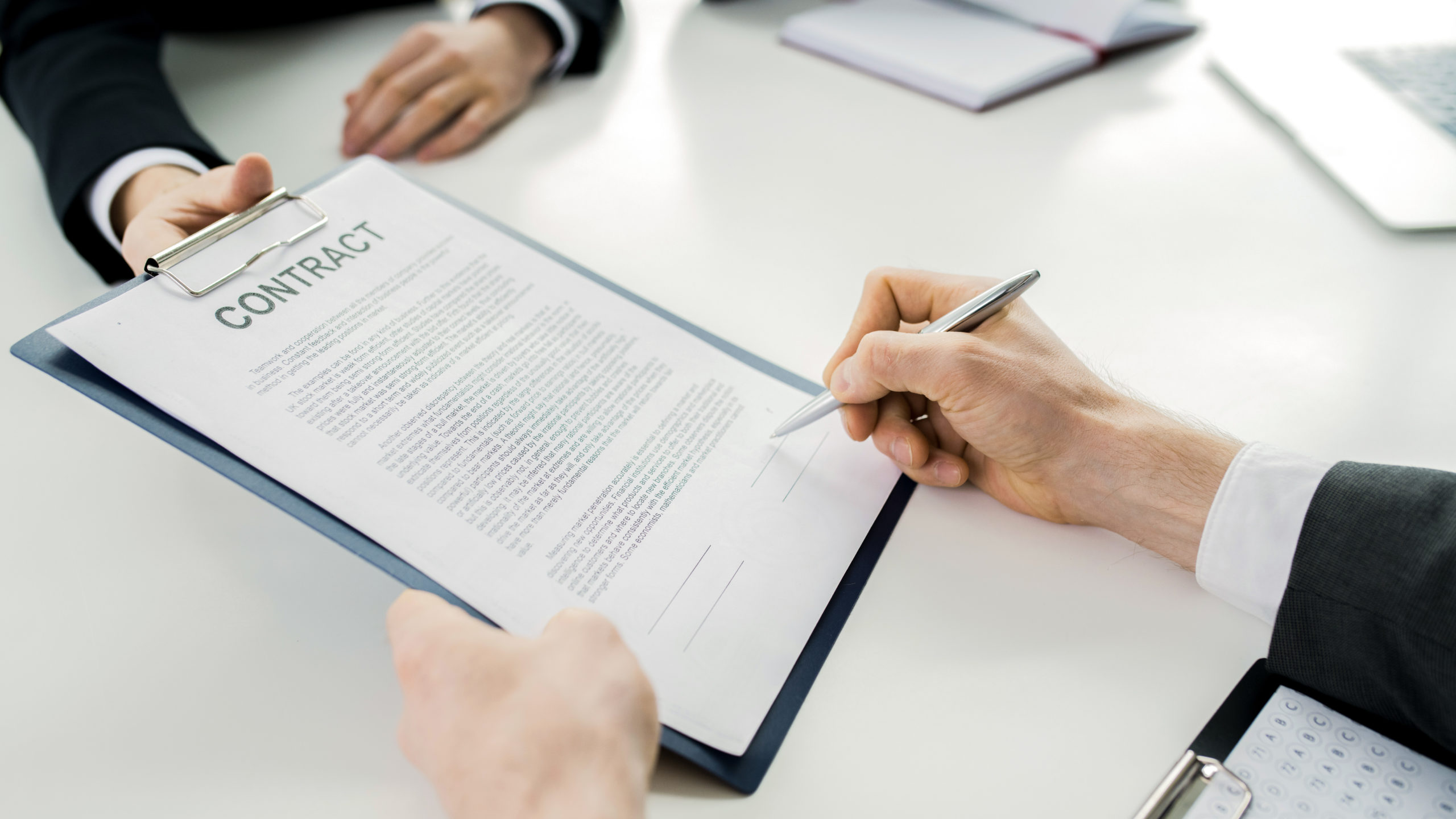 Close up of unrecognizable businessman signing contract during meeting with partners at table in conference room, copy space