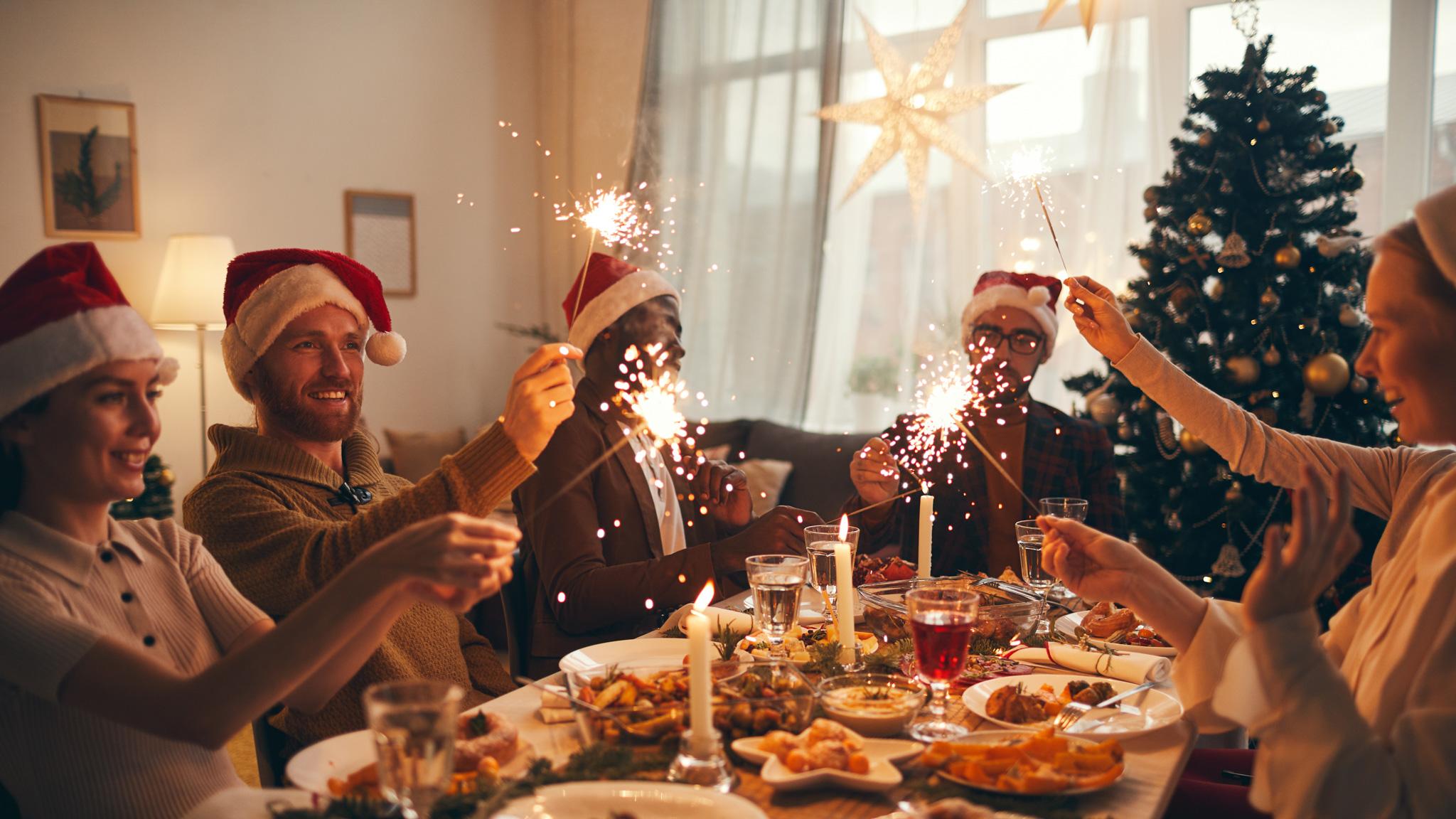 Multi-ethnic group of people raising glasses while enjoying Christmas dinner at home