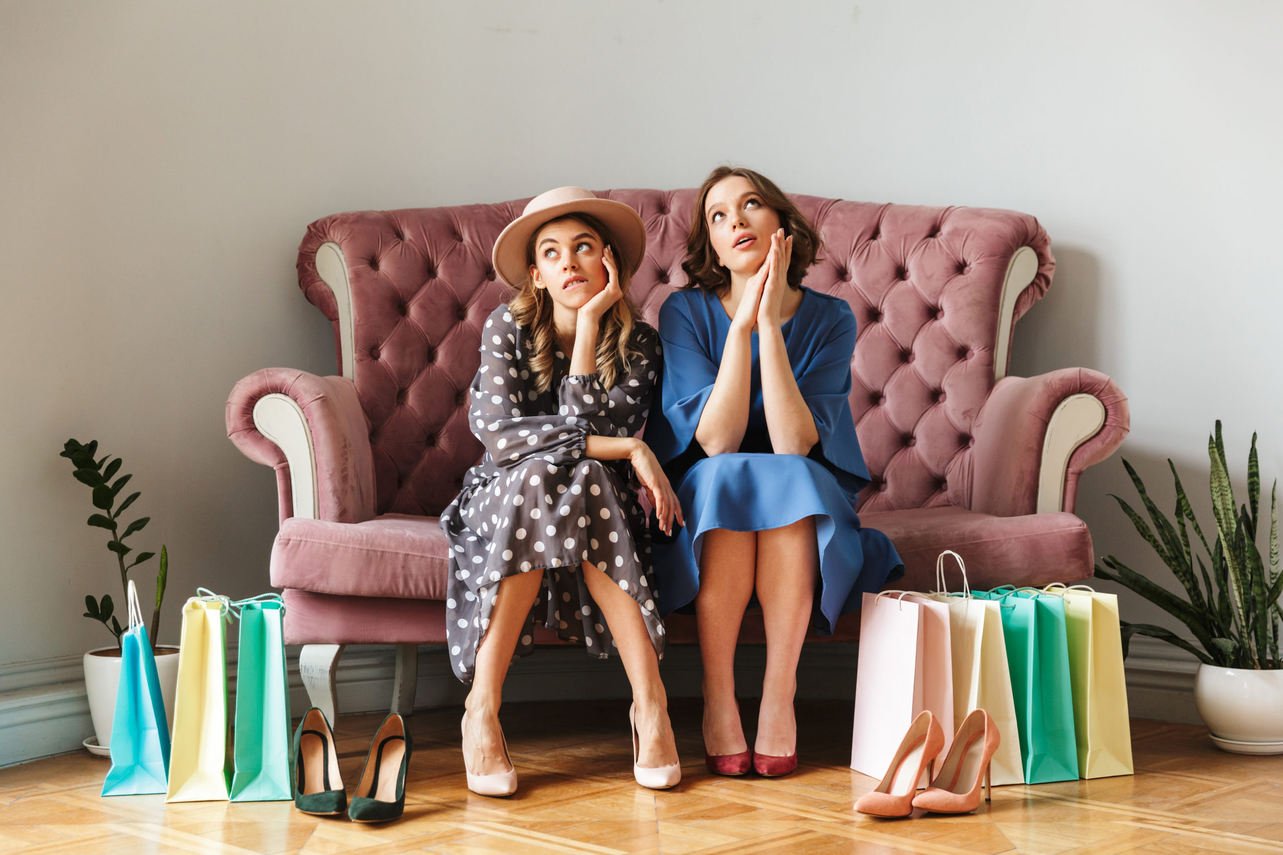 Image of two thinking young women shopaholics sitting indoors in shop showroom with shopping bags.